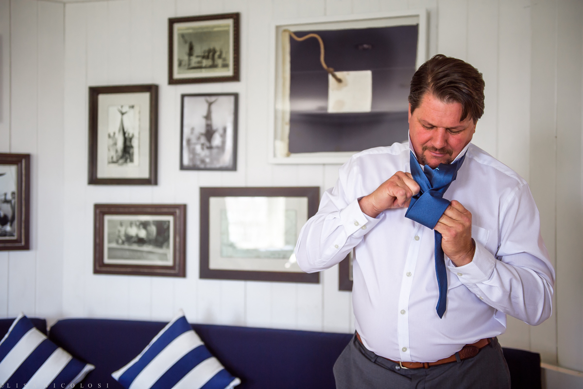 Groom putting on tie at Montauk Yacht Club
