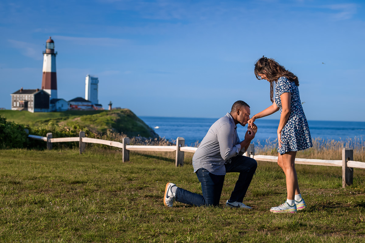 Montauk Surprise Proposal - Groom kneeling and kissing bride's hand