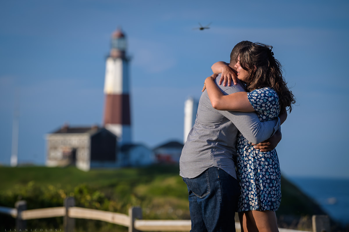 Couple hugging after he proposes in front of Montauk Lighthouse