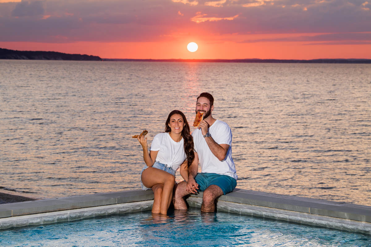 Natural Hamptons Engagement photography - Couple eating pizza by infinity pool