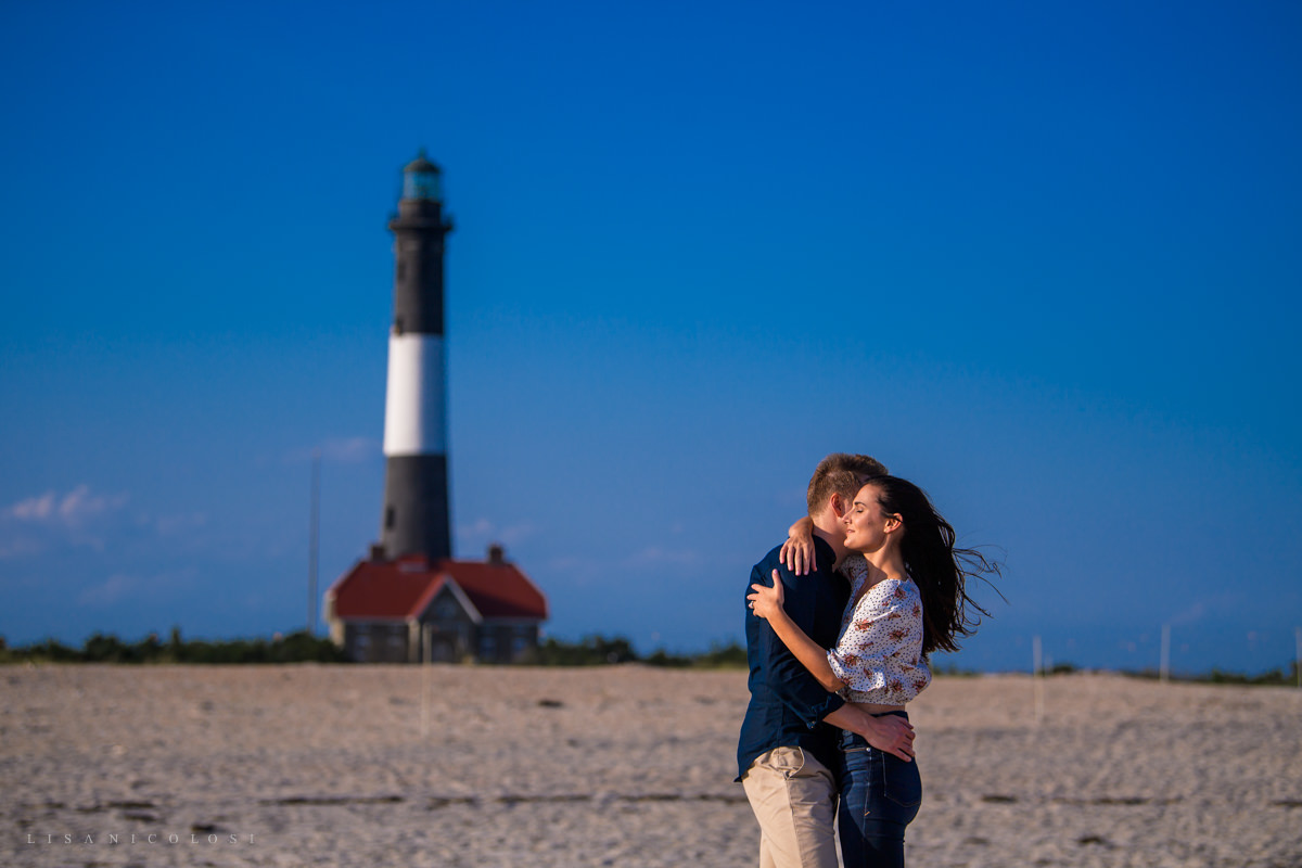 Engagement portraits at Robert Moses State Park with Fire Island Lighthouse in background