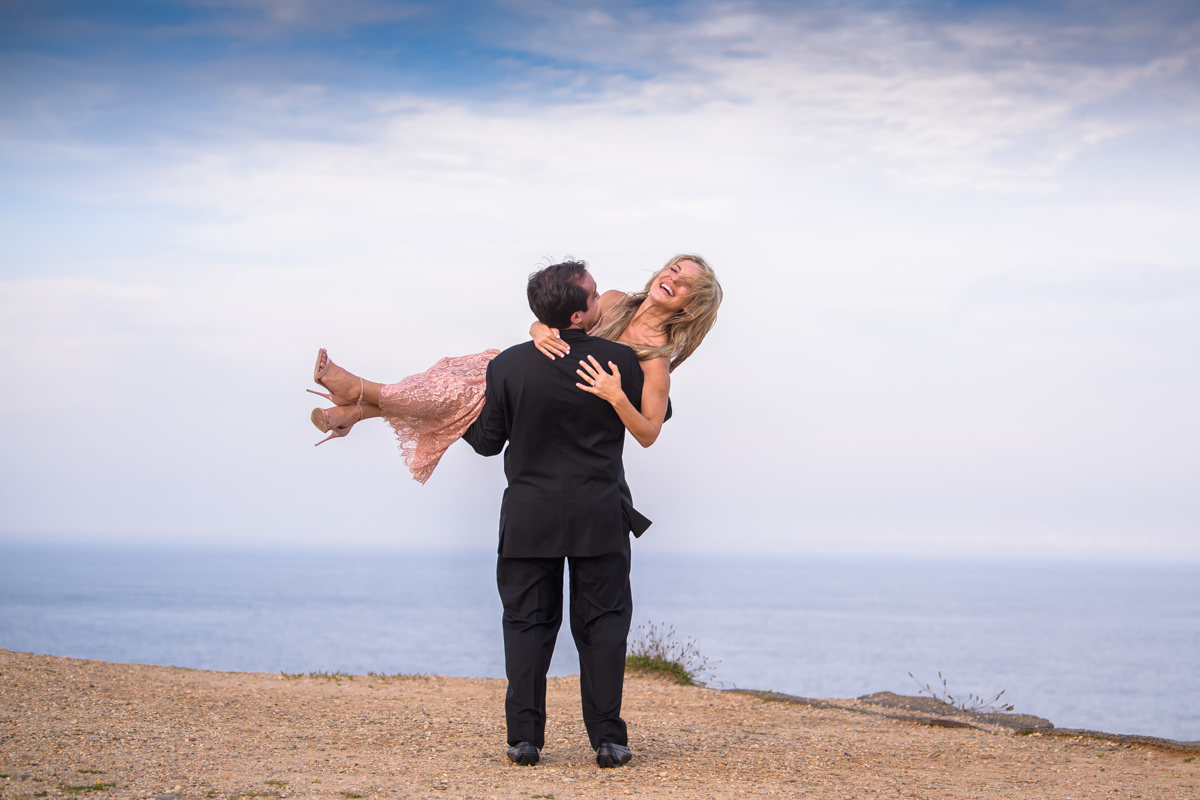 Engagement portrait of groom lifting his bride at Camp Hero State Park in Montauk
