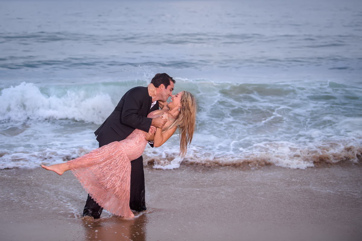 fun beach engagement session of bride and groom playing in Ocean