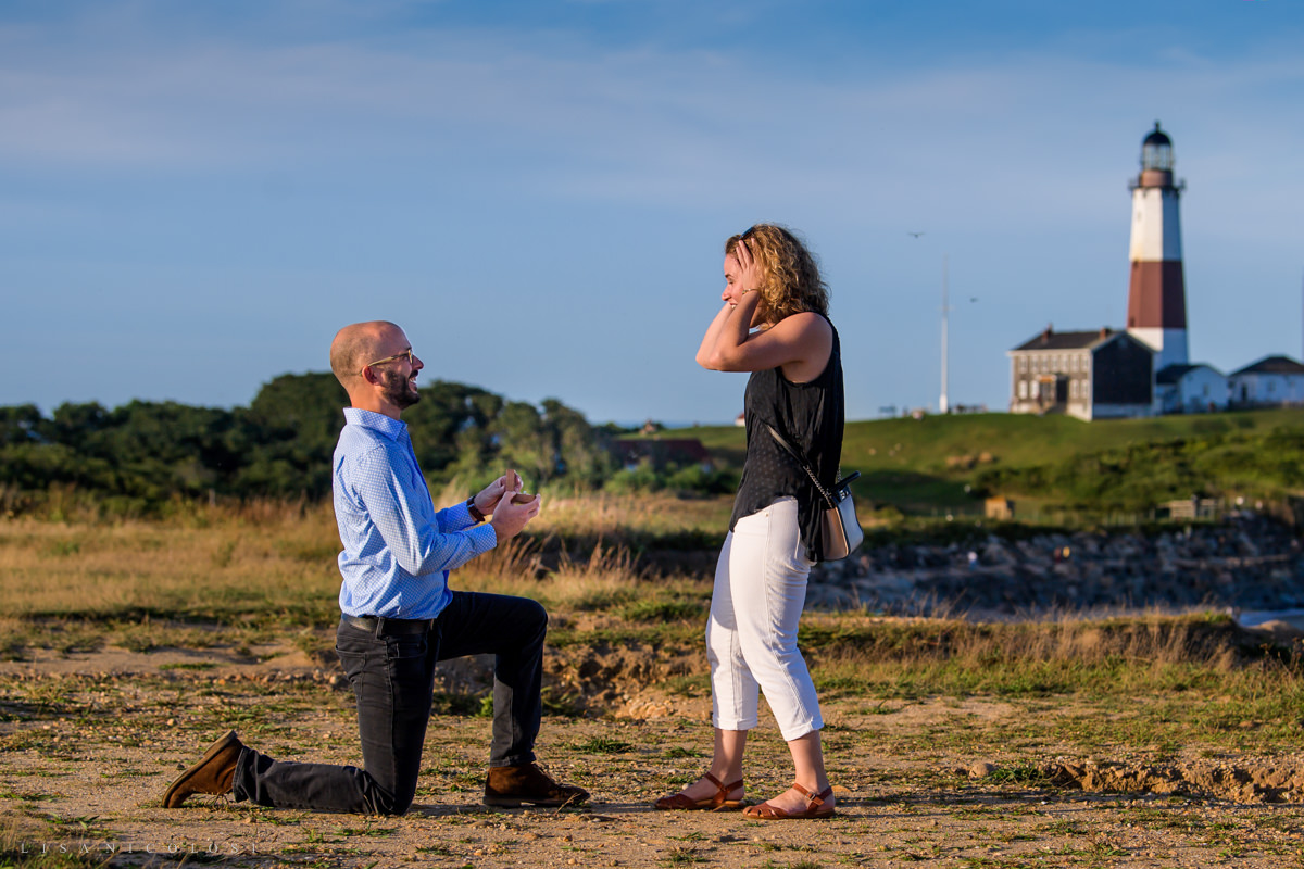 Groom kneels to propose to girlfriend in Montauk proposal photography session. Girlfriend is shocked.