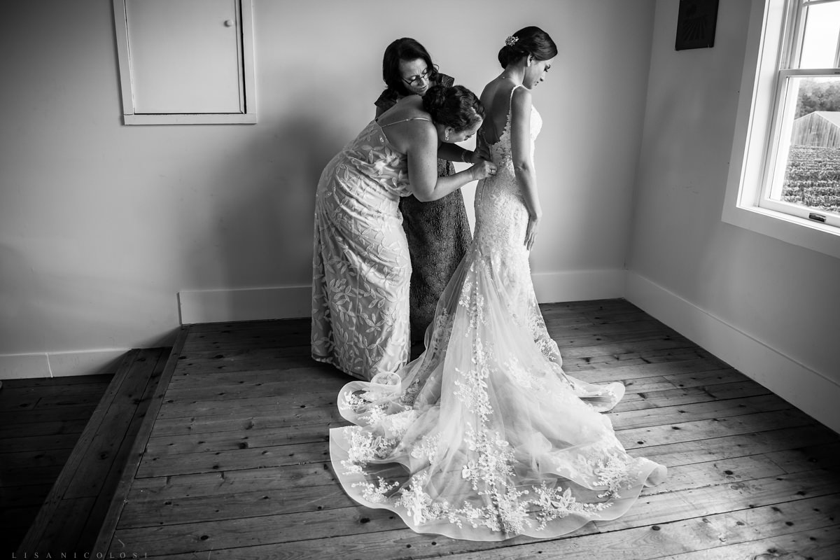 mother and sister of the bride helping her get into wedding gown