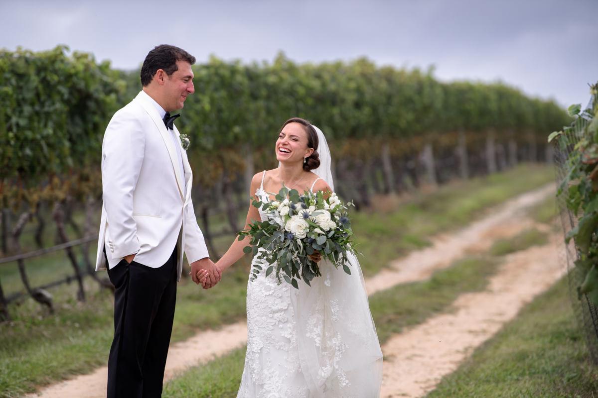 Bride and groom laughing in vines at Pellegrini Vineyards