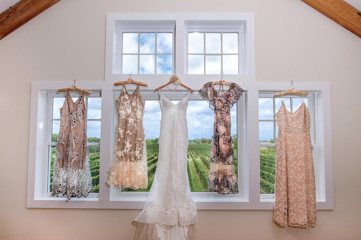 Bride's gown and bridesmaids dresses hanging in bridal suite at Pellegrini Vineyards