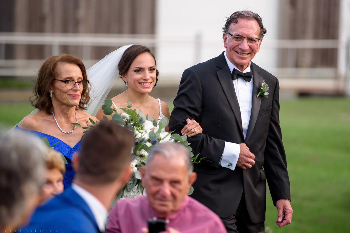 Wedding processional at Pellegrini Vineyards - Bride smiling with her parents