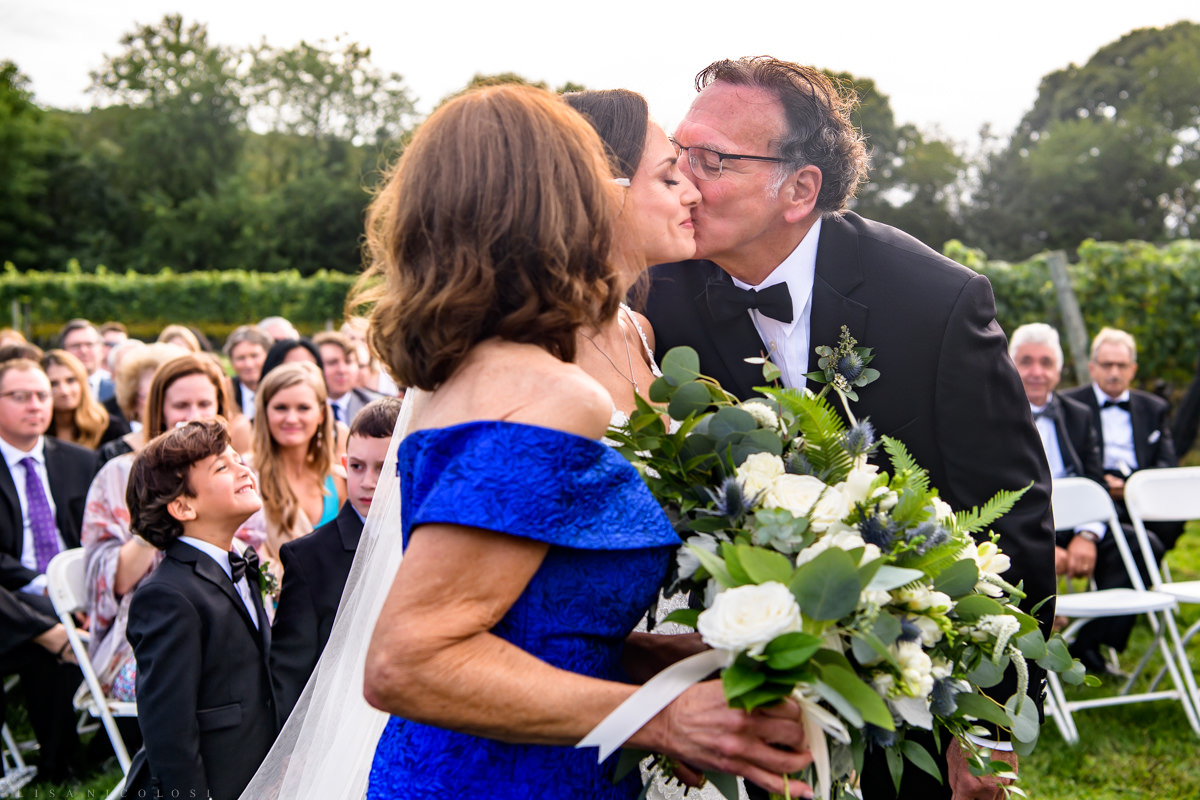 Wedding processional at Pellegrini Vineyards - parents giving away bride with a kiss
