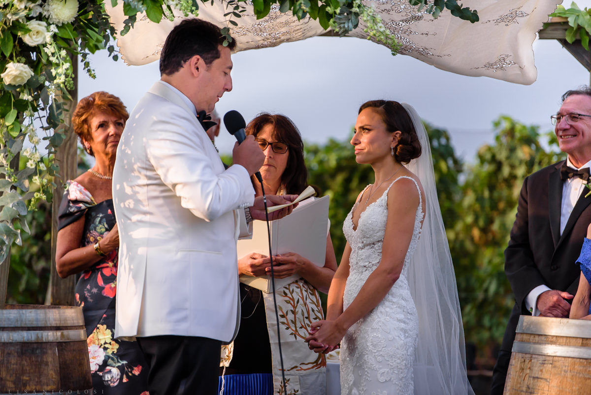 Wedding ceremony at Pellegrini Vineyards in Cutchogue - groom saying vows