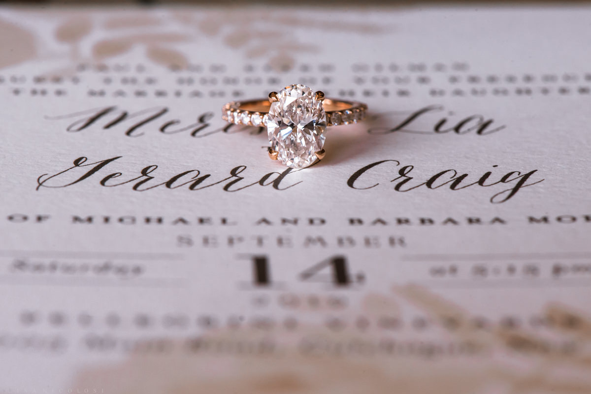 The bride's engagement ring and wedding invitation