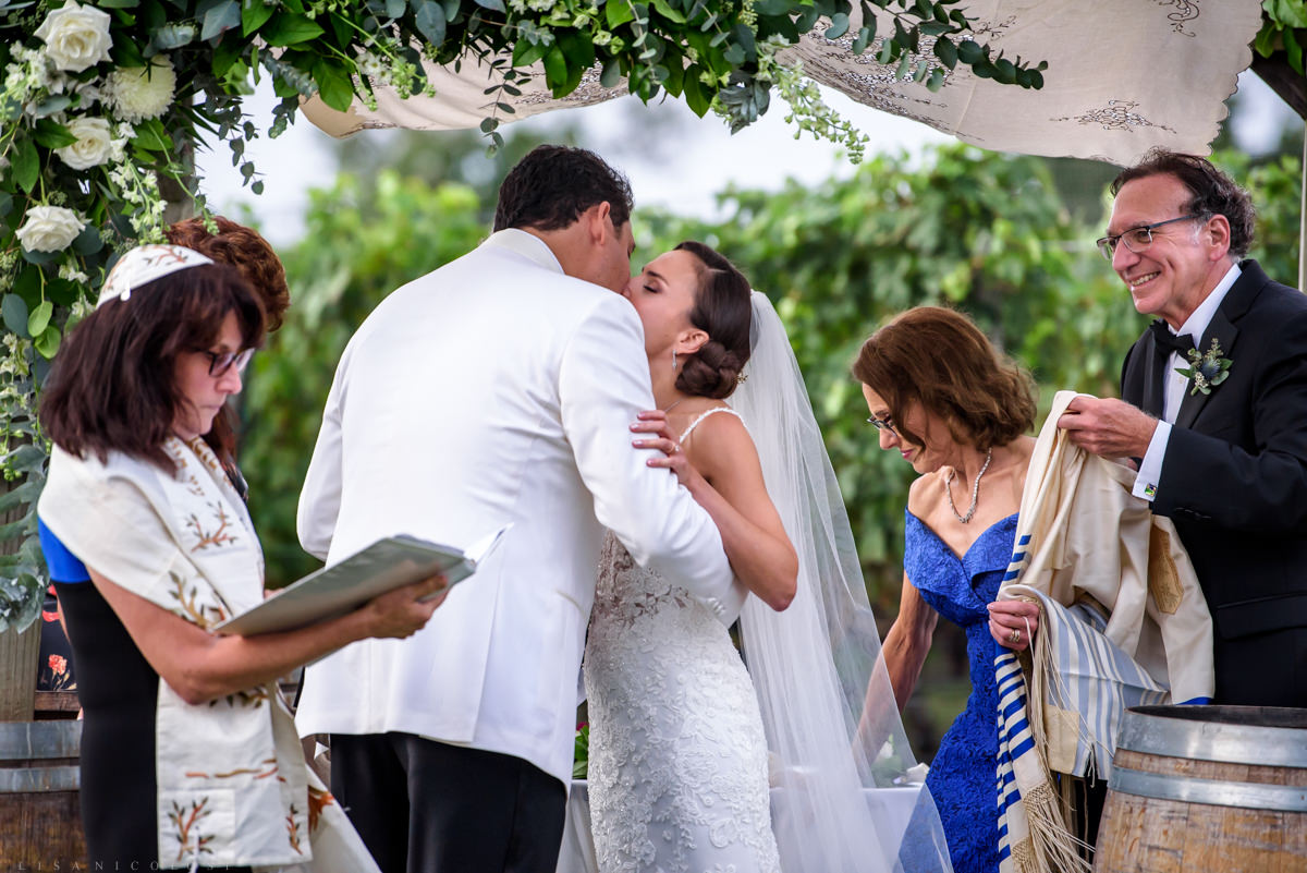 Wedding ceremony at Pellegrini Vineyards in Cutchogue - bride and groom kissing