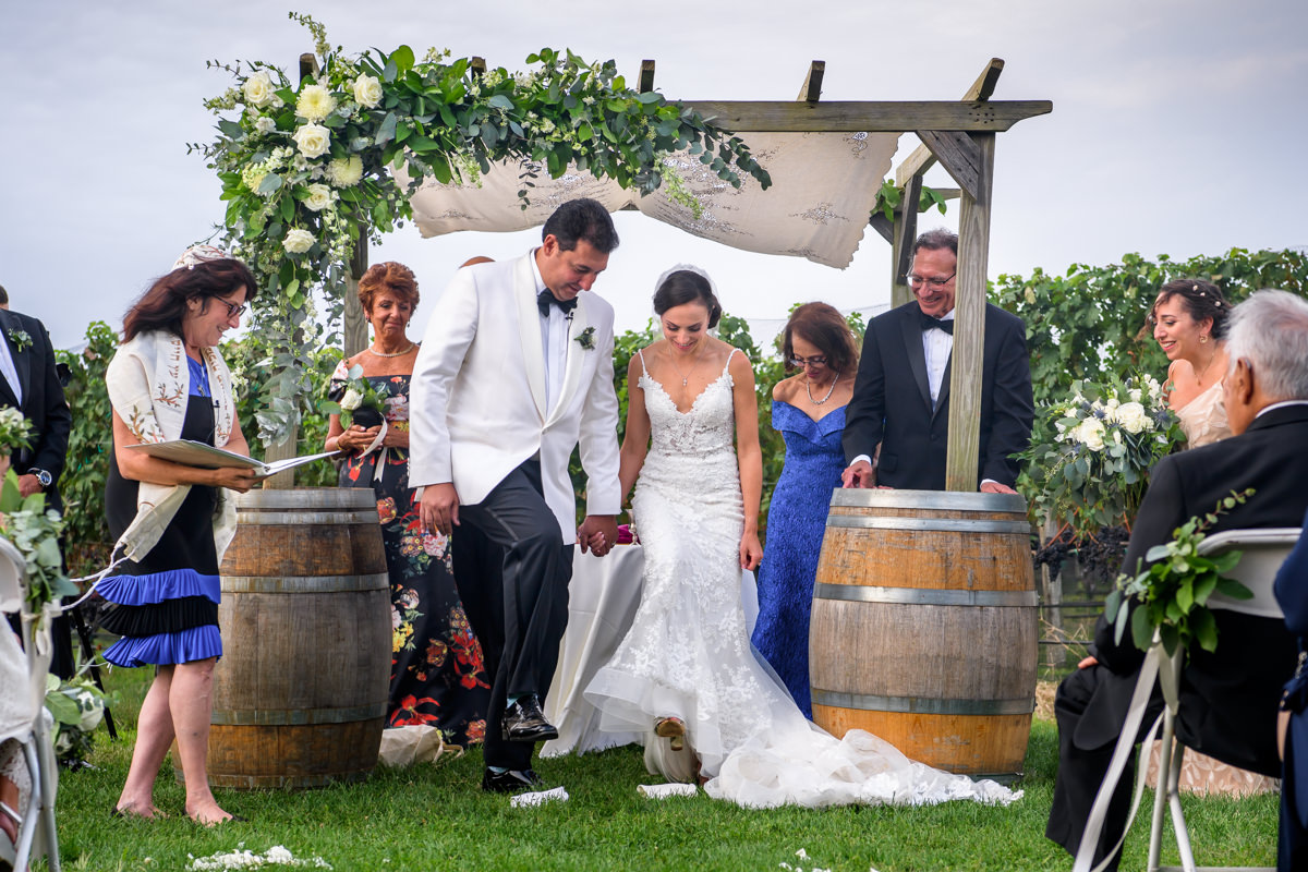 Wedding ceremony at Pellegrini Vineyards in Cutchogue - Bride and groom breaking glass together
