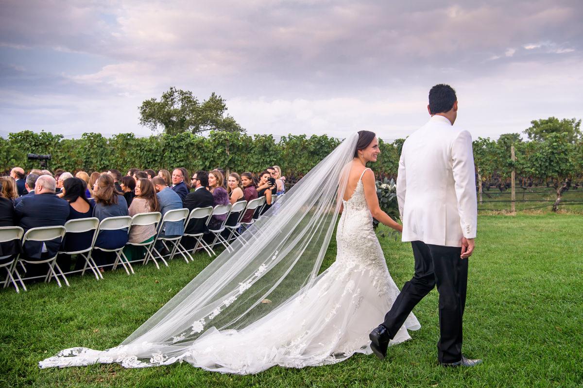 Wedding Ceremony recessional at Pellegrini Vineyards _ Bride and groom walking away