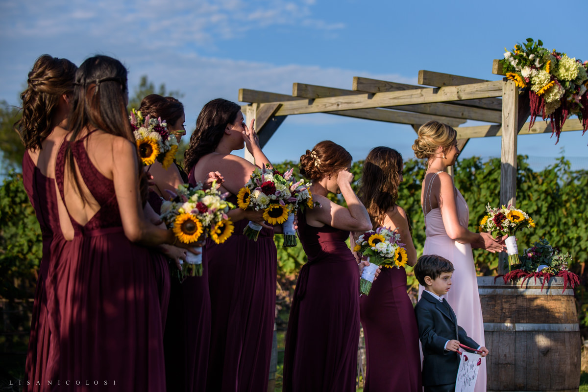 Wedding Ceremony at Pellegrini Vineyards - bridesmaids wiping tears from their eyes