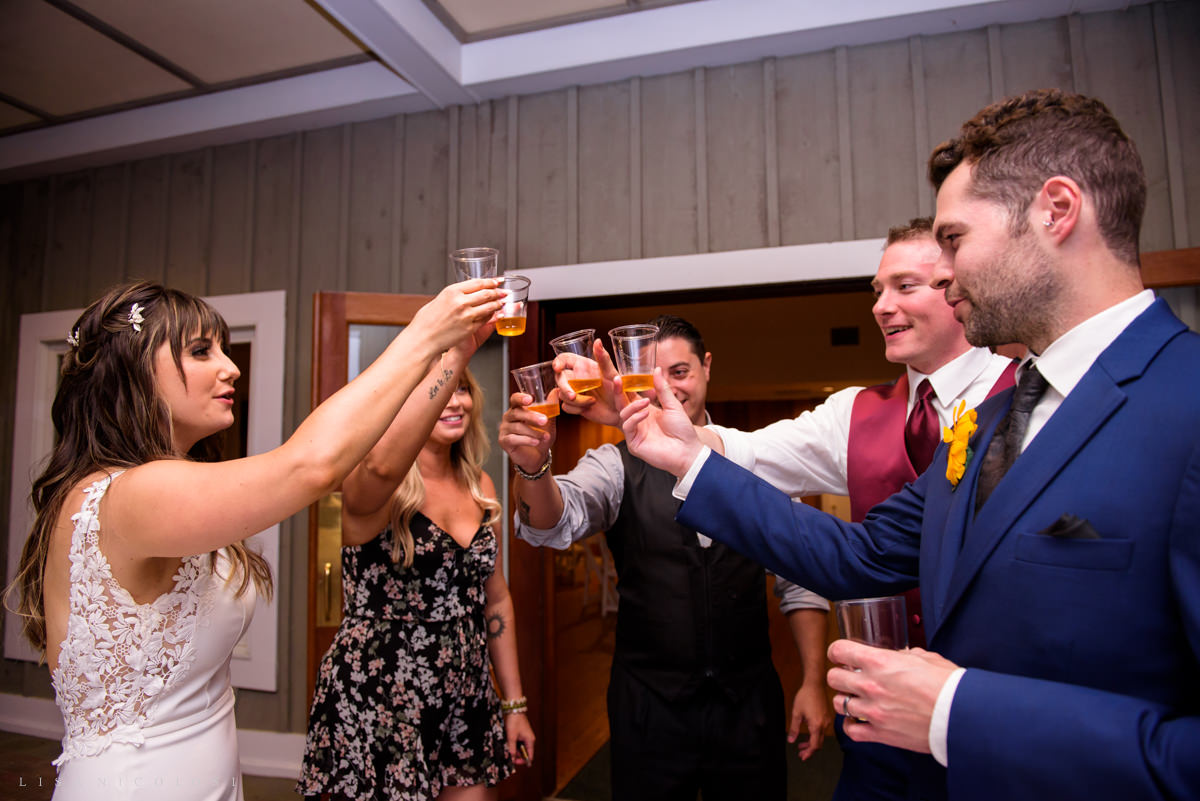 Bride and groom toasting shots with guests