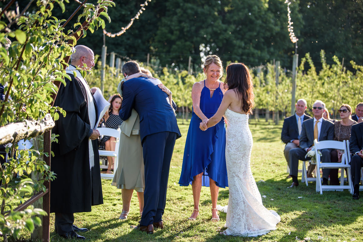 Jamesport Manor Inn Wedding Ceremony in the apple orchard - bride and groom with their moms