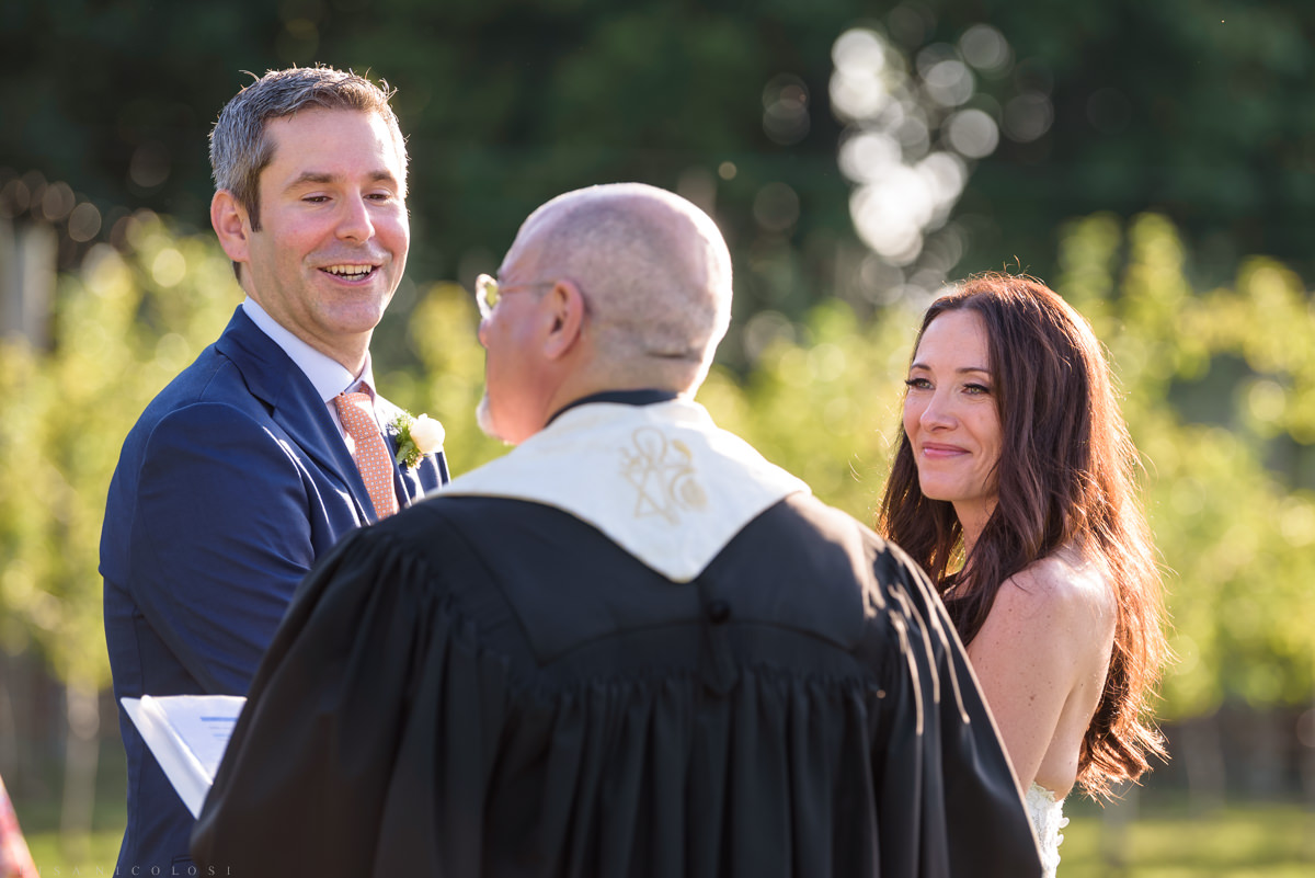 Jamesport Manor Inn Wedding Ceremony in the apple orchard- bride and groom laughing