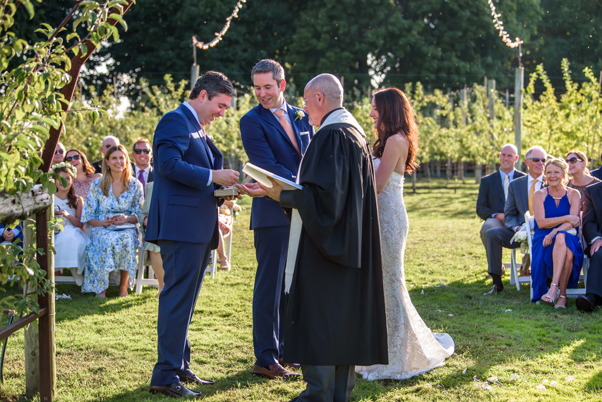 Jamesport Manor Inn Wedding Ceremony in the apple orchard - Best man getting out rings