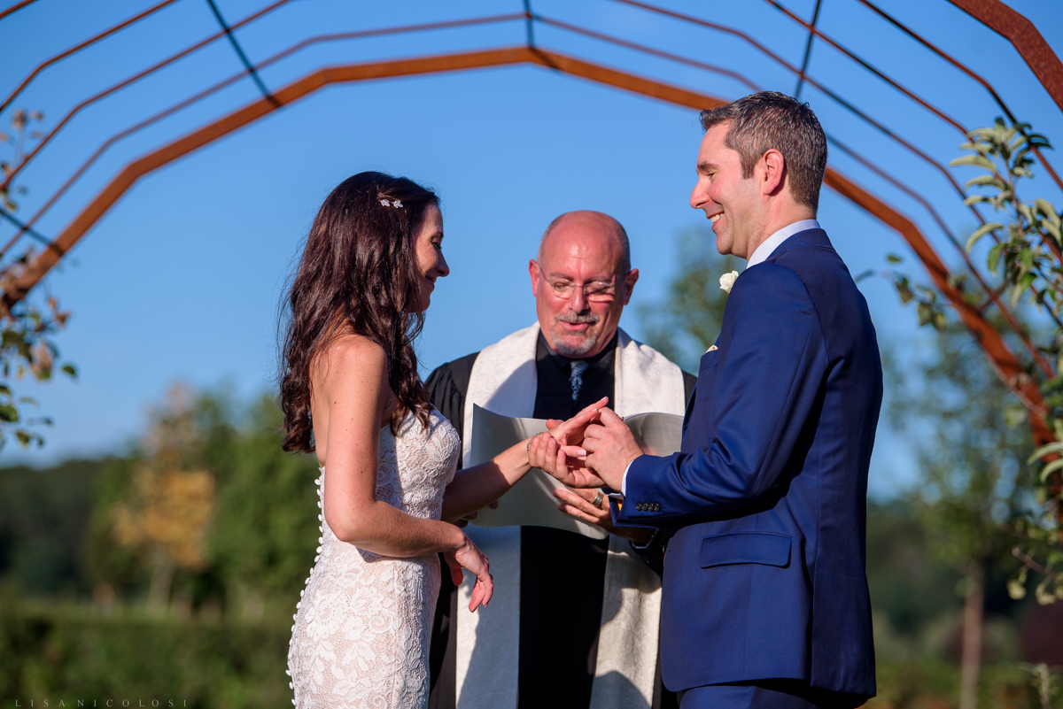 Jamesport Manor Inn Wedding Ceremony in the apple orchard - bride and groom exchanging rings