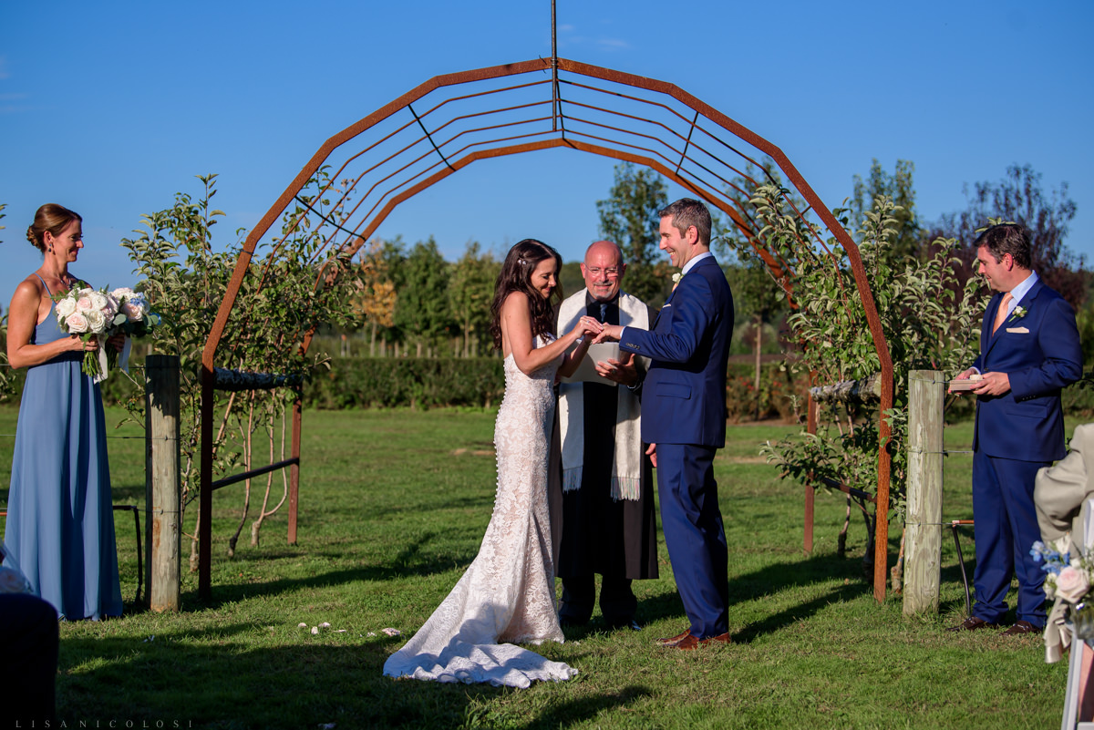 Jamesport Manor Inn Wedding Ceremony in the apple orchard - bride placing ring on gtoom