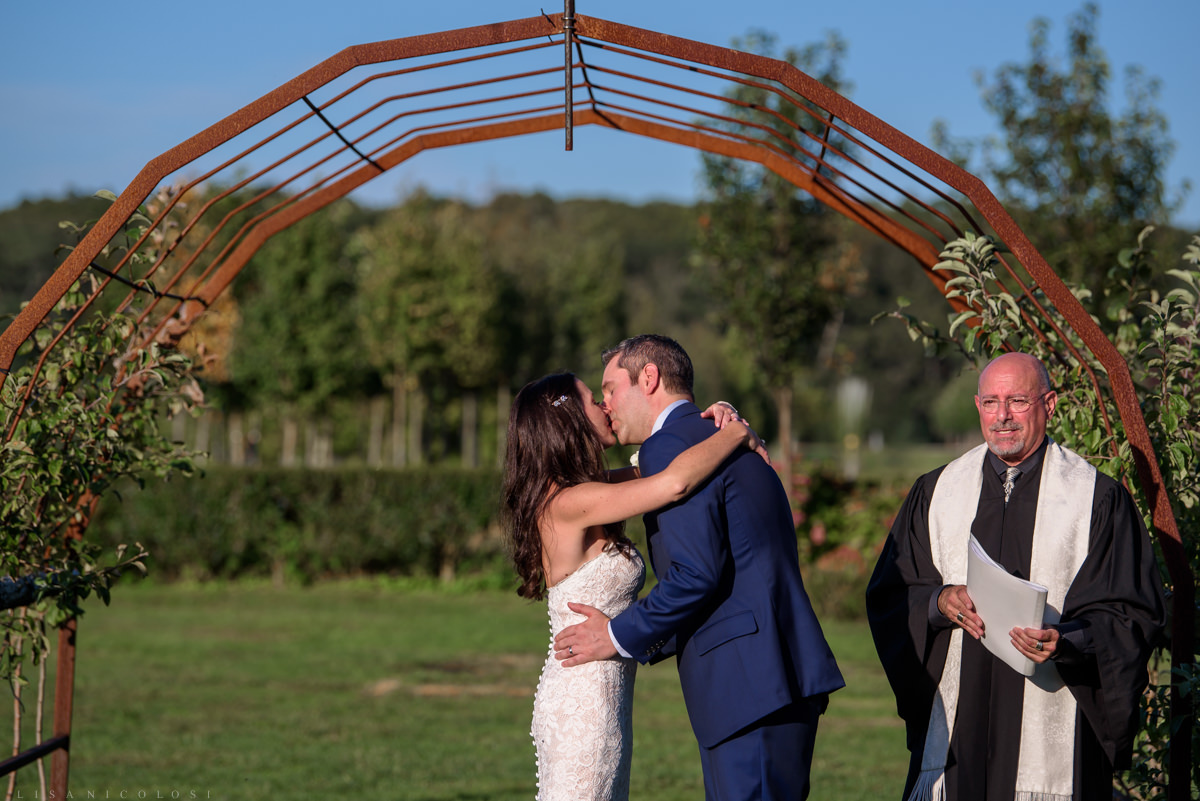 Jamesport Manor Inn Wedding Ceremony in the apple orchard - bride and groom kissing
