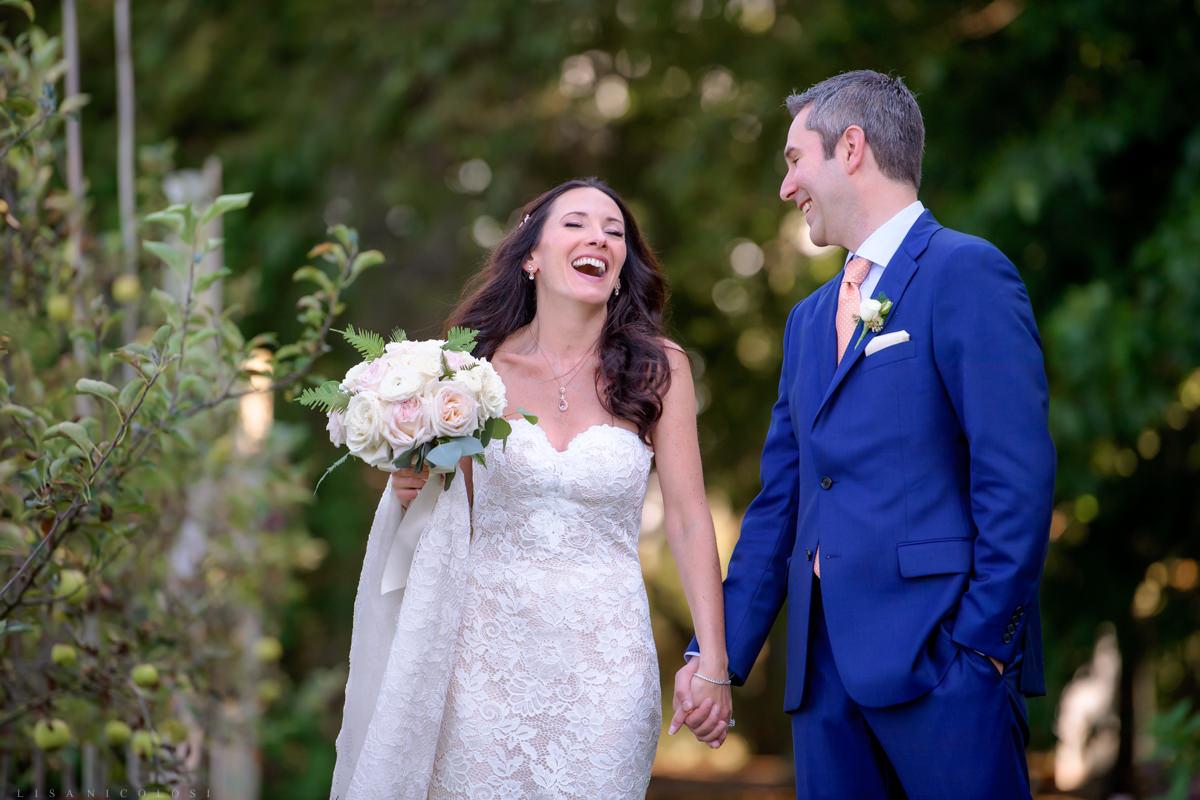 Jamesport Manor Inn Wedding - Bride and groom walking in the apple orchard