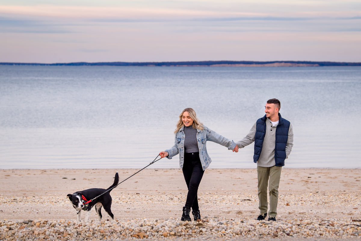 Engaged couple walking their dog in Hampton Bays