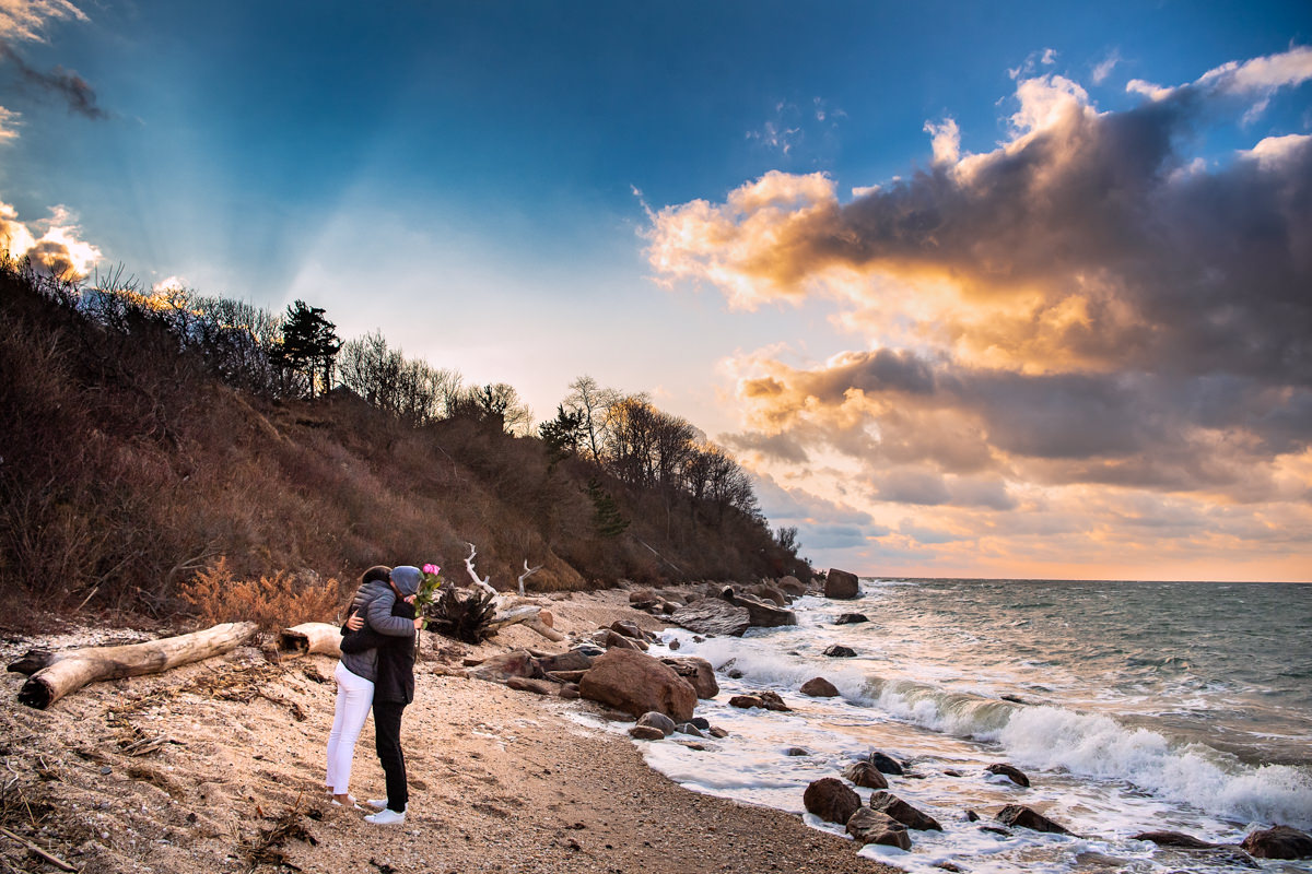 Greenport Proposal Photographer - Bride and groom become engaged on the beach in Greenport