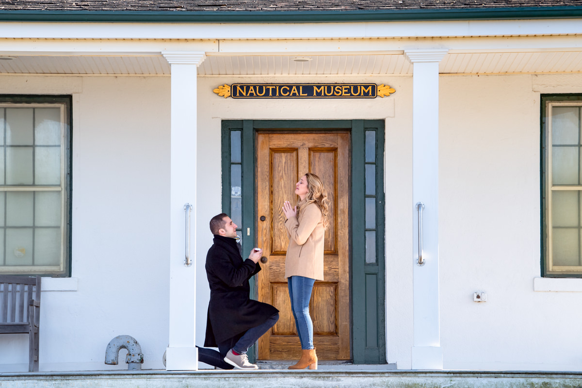 Groom to be kneels to propose marriage - North Fork Marriage Proposal at Horton Point Lighthouse Nautical Museum