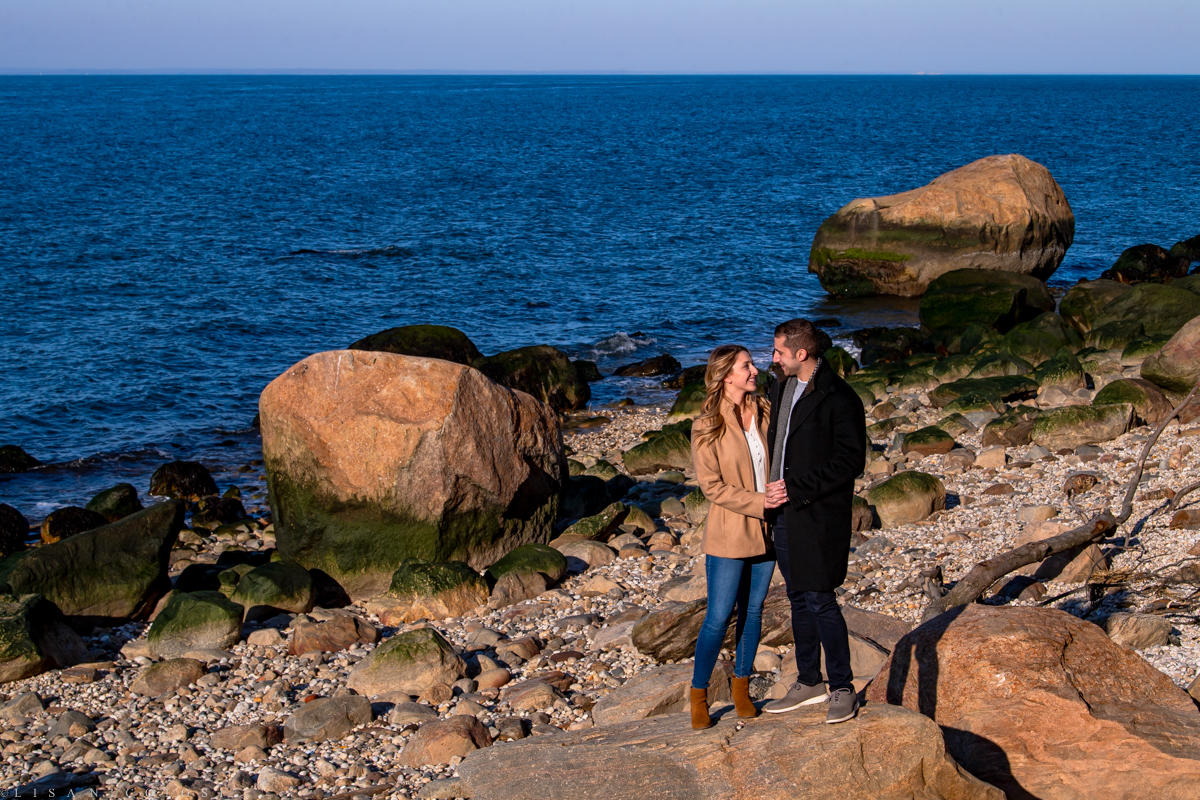 Couple standing on rocks on the beach in Southold