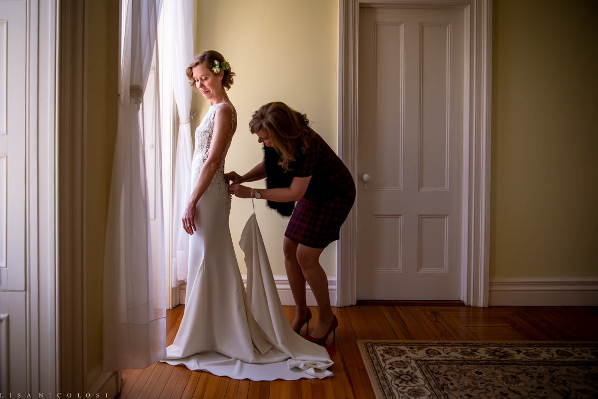 Brecknock Hall Wedding - Maid of honor buttoning bride's wedding dress