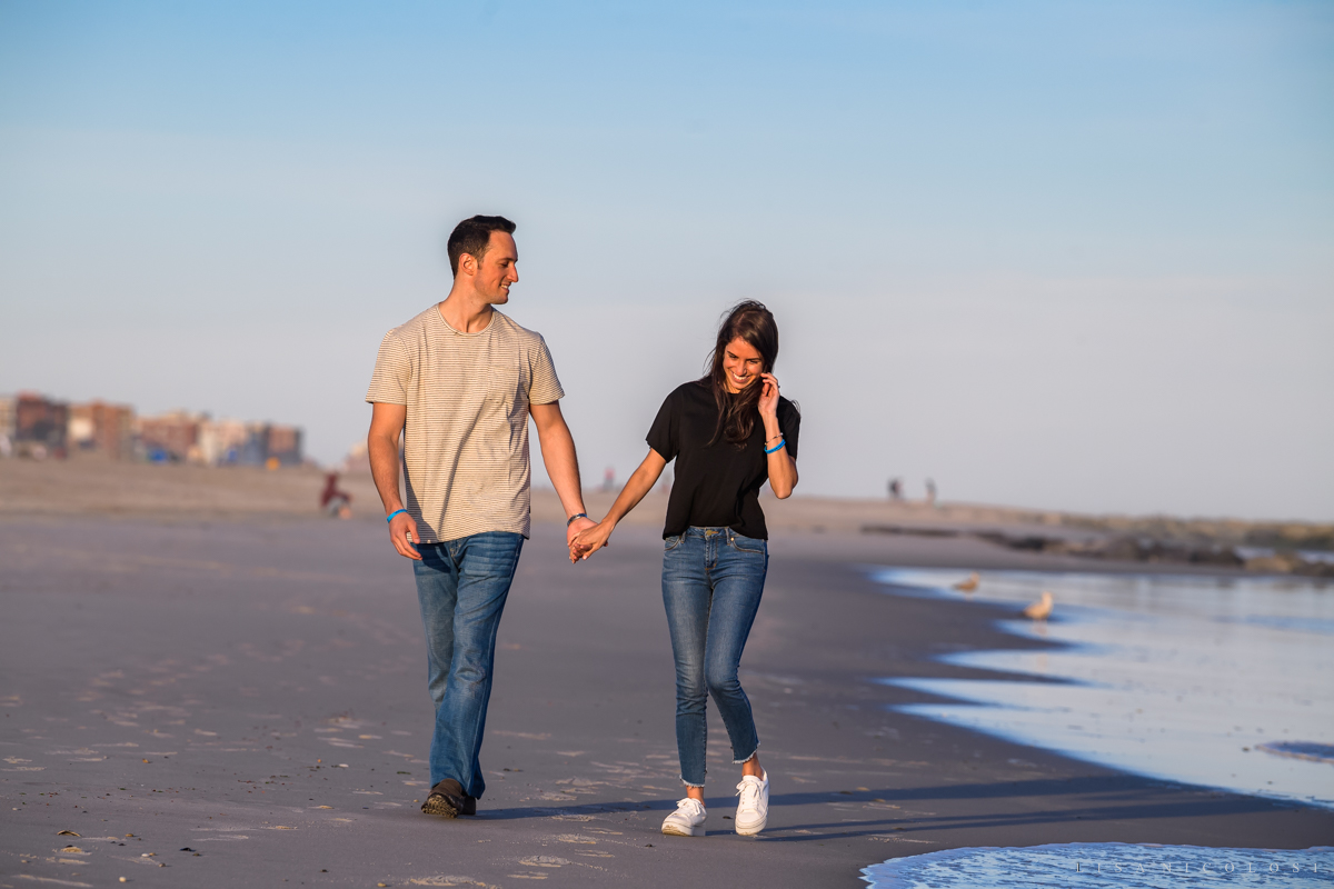 couple walking on beach -Fun Engagement Photos at Atlantic Beach NY - Long Island Proposal Photographer