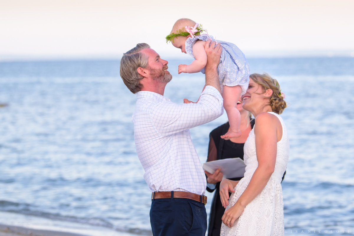 Bride and Groom holding baby at beach wedding ceremony in Jamesport NY