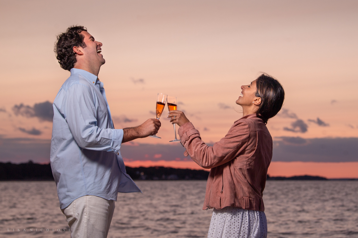 Sag Harbor Proposal and Engagement Portraits at Foster Memorial Beach during sunset - Toasting Champagne glasses