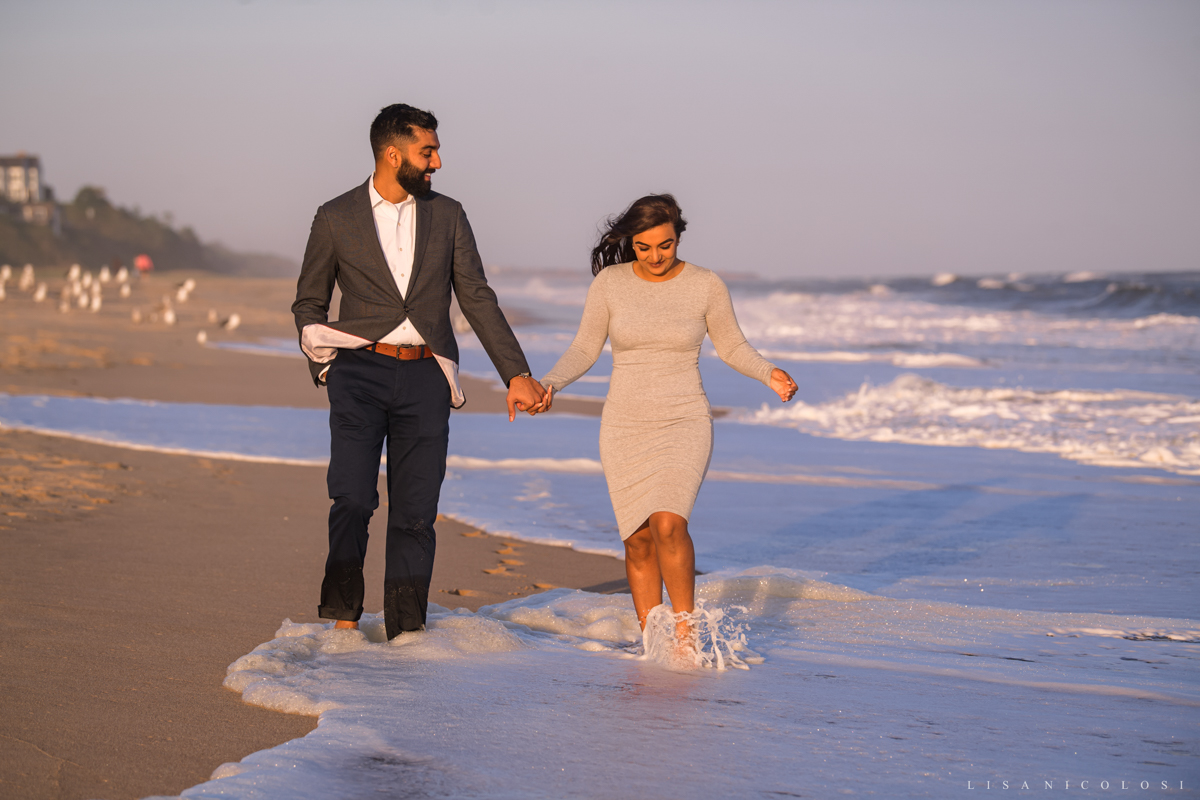 Engaged couple walking on the beach at Gurney's Resort