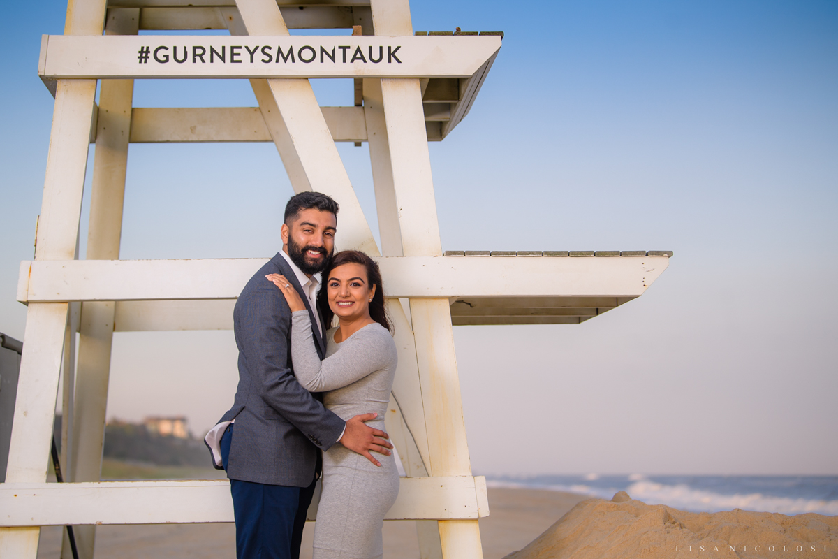 Gurney's Resort Proposal Photographer - Couple posing by Lifeguard Chair