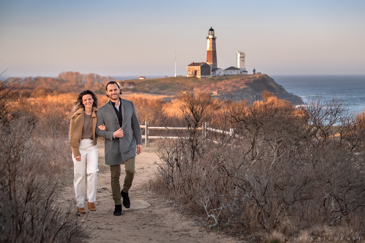 Happy couple walking on the bluffs in Montauk with the Lighthouse in the background
