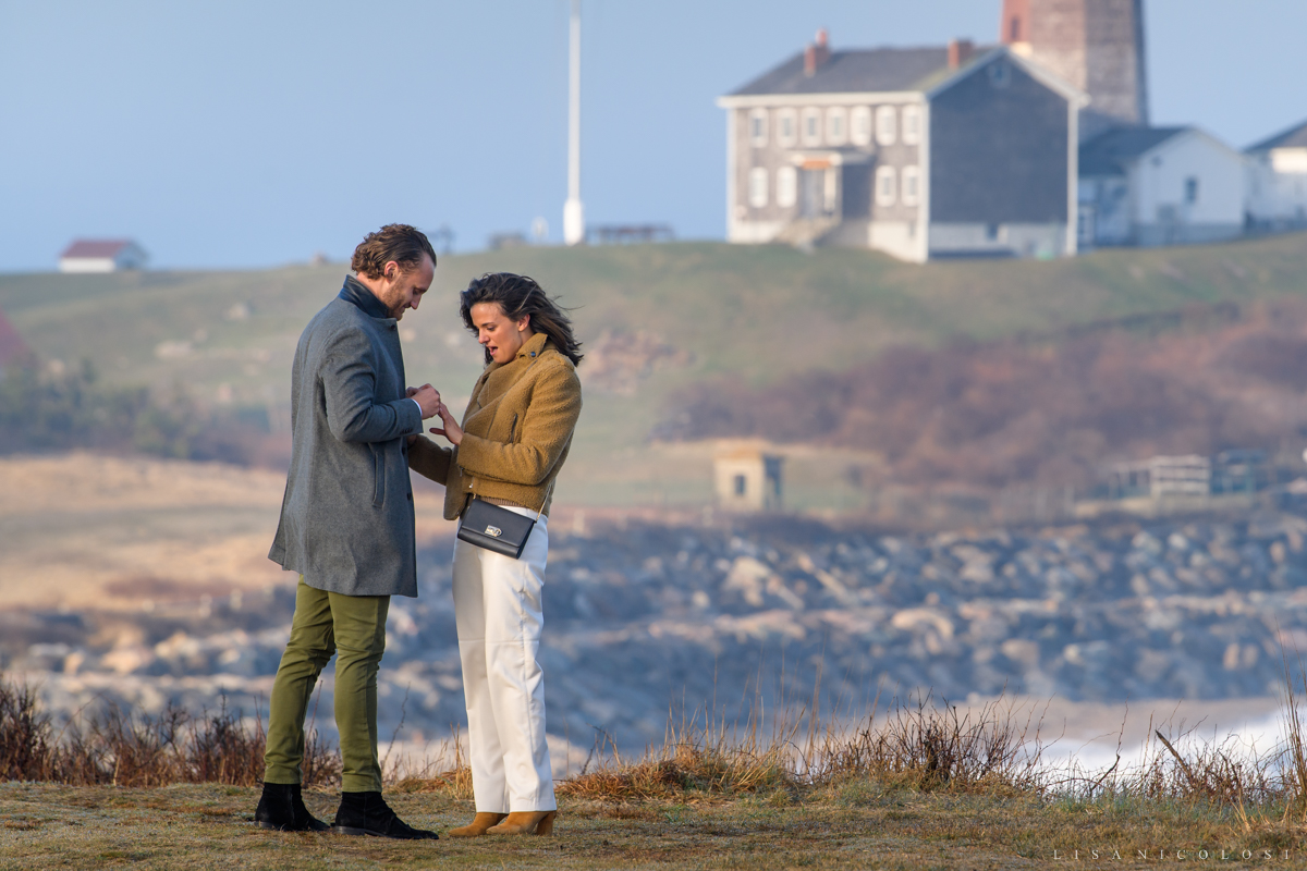 Groom to be placing ring on his bride's finger | Montauk engagement photographer